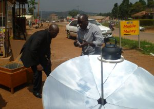 Mukasa (on the right) explains the parabolic cooker to Seydou Coulibaly, director of the Togo Tilé project in Mali.