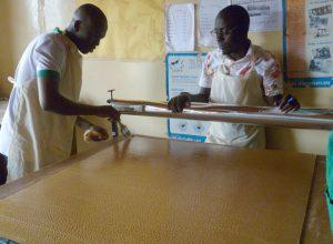 Mukasa (à droite) donne des instructions sur la fabrication du CooKit à Seydou Coulibaly, directeur du projet de Togo Tilé au Mali.