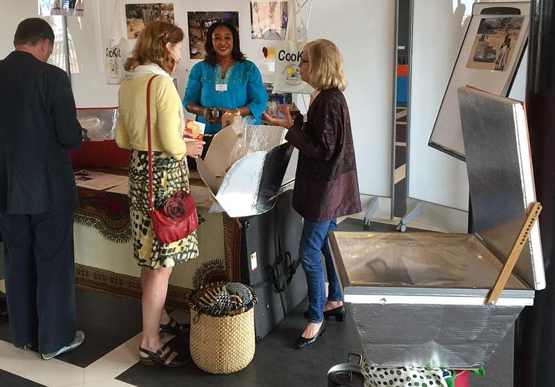 Wilma Goppel (rechts) en Fatim Diaw (midden) geven een bezoekster uitleg over het gebruik van de CooKit.
